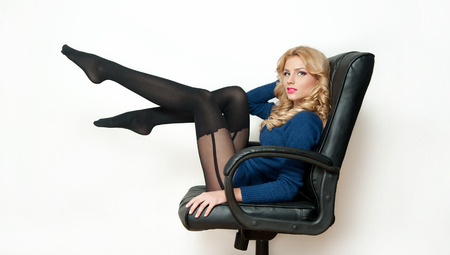 Attractive sexy blonde female with bright blue blouse and black stockings posing smiling sitting on office chair  Portrait of sensual fair hair woman with long legs isolated on white background