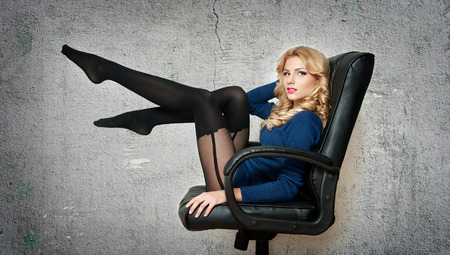 Attractive sexy blonde female with bright blue blouse and black stockings posing smiling sitting on office chair  Portrait of sensual fair hair woman with long legs isolated on gray background Stock Photo