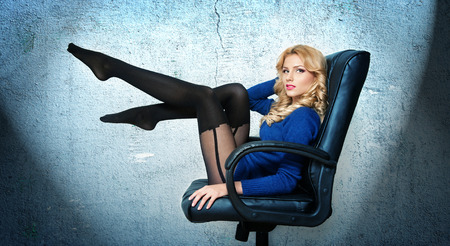 Attractive sexy blonde female with bright blue blouse and black stockings posing smiling sitting on office chair  Portrait of sensual fair hair woman with long legs isolated on blue background