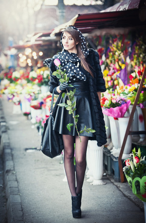 Beautiful brunette woman with gloves holding a rose in front of  florist shops  Fashionable female with head scarf and long legs at flower shop  Pretty brunette in black choosing flowers - urban shot photo