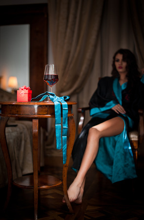 Beautiful sexy woman with glass of wine sitting on chair  Portrait of a woman with long curly hair posing challenging  Sexy brunette sitting near wood table with glass with red wine in vintage scene photo
