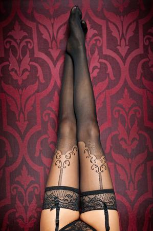 plan �loign�: De longues jambes dans des bas noirs et des culottes tir int�rieur femme sexy jambes
