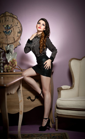 Young beautiful woman in black in a vintage room Beautiful young woman with long legs in a classic interior  Seductive woman wearing short black skirt and high heels in luxury manor, vintage style photo