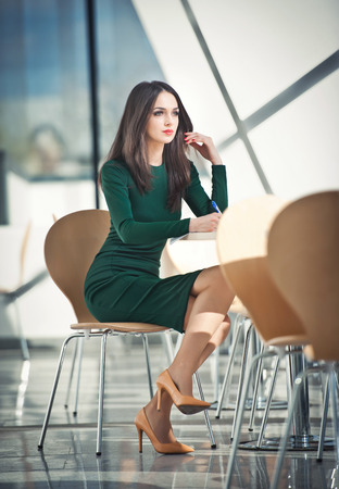 Fashion attractive girl in dark green dress sitting on chair writing, indoor shot  Modern urban scenery  Fashion art photo of sensual lady in glass and steel scenery  Girl with high heels at table photo