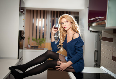 Attractive sexy blonde female with bright blue blouse and black stockings posing smiling holding a glass with red wine  Portrait of sensual fair hair woman with long legs in modern kitchen