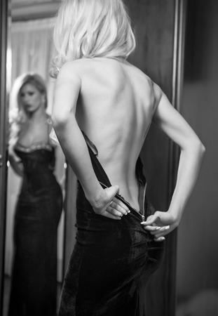 Young beautiful luxurious woman zipping up her long elegant black dress looking in a large mirror  Back side view, black and white photo  Seductive blonde woman in luxury manor, vintage style