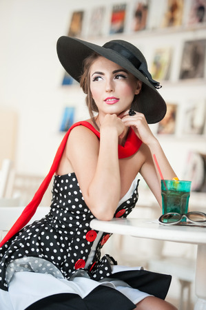 french model: Fashionable attractive lady with black hat and red scarf sitting on chair in restaurant, indoor shot  Young woman posing in elegant scenery  Art photo of elegant sensual woman, vintage style