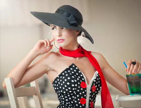 Fashionable attractive lady with black hat and red scarf sitting on chair in restaurant, indoor shot  Young woman posing in elegant scenery  Art photo of elegant sensual woman, vintage style photo