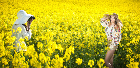 Young girl wearing Romanian traditional blouse and hat posing in canola field, outdoor shot  Lady photographer shooting beautiful blonde smiling and enjoying the bright yellow flowers of rapeseed photo
