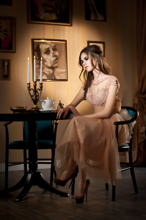 Young beautiful brunette woman in elegant lace dress sitting near a table with candlestick  Long hair attractive girl in luxurious classic interior  Seductive female in vintage scenery, indoor photo