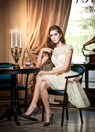 Young beautiful brunette woman in elegant lace dress sitting near a table with candlestick  Long hair attractive girl in luxurious classic interior  Seductive female in vintage scenery, indoor