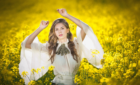 Young girl wearing elegant white blouse posing in canola field, outdoor shot  Portrait of beautiful long hair brunette with large transparent sleeves in bright yellow rapeseed field, spring scenery photo