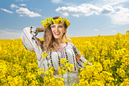 Young girl wearing Romanian traditional blouse posing in canola field with cloudy sky in background, outdoor shot  Portrait of beautiful blonde with flowers wreath smiling in rapeseed field