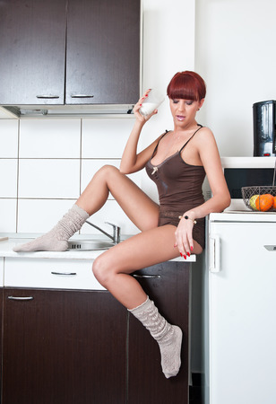 Attractive sexy woman in shirt and socks drinking milk in kitchen photo