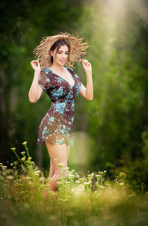 Pretty young woman wearing a straw hat posing in forest  Very attractive brunette girl with short dress, outdoor shot  Romantic female in the field during shiny day  photo