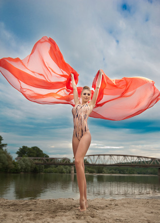 Lovely young lady posing dramatically with long red veil in summer scenery  Blonde woman with cloudy sky and bridge in background - outdoor shoot  Glamorous female in nature - creative shot photo