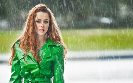 Beautiful woman in bright green coat posing in the rain  Dramatic redhead staying in the rain drops, urban shot  Attractive red hair girl on the street in a rainy day  Emotional pretty young female  photo