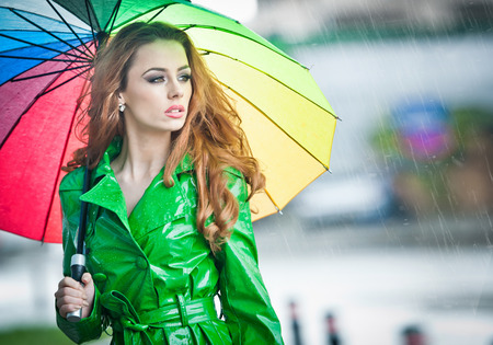 Beautiful woman in bright green coat posing in the rain holding a multicolored umbrella  Dramatic redhead staying under umbrella, urban shot  Attractive red hair girl on the street in a rainy day