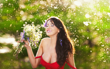 low blouse: Young voluptuous brunette holding  a wild flowers bouquet in a sunny day  Portrait of beautiful woman with low-cut red dress laughing, outdoor shot  Provocative female enjoying the nature Stock Photo