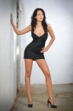Charming young brunette woman in black tight fit dress posing against a wall  Sexy gorgeous young woman with high heels  Full length portrait of a provocative woman with long hair and sporty allure