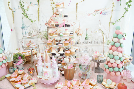Wedding decoration with pastel colored cupcakes, meringues, muffins and macaroons
