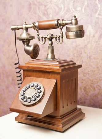 Old wooden phone  Vintage wooden telephone on white table  Retro phone  photo