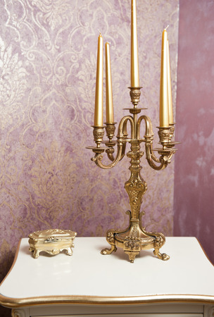 Golden candlestick with five candles on white table, in front of luxurious textured wall
