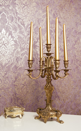 candelabrum: Golden candlestick with five candles on white table, in front of luxurious textured wall