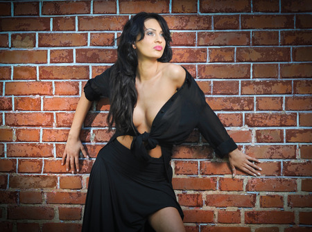 low blouse: Charming young brunette woman in black near the brick wall