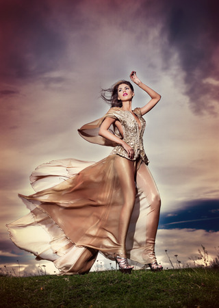 elegance fashion girls look sensuality young: Fashionable beautiful young woman in nude colored long dress posing outdoor with cloudy dramatic sky in background  Attractive long hair brunette girl with elegant luxurious dress, outdoors shot