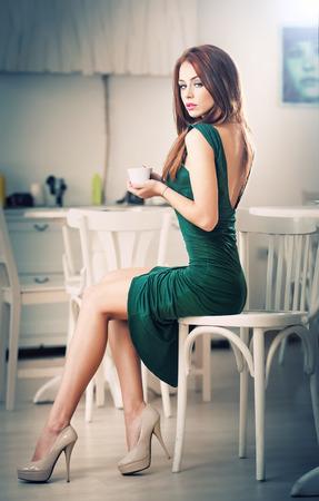 mujer elegante: Mujer de moda joven y atractiva en vestido verde sentada en el restaurante y bella pelirroja posando en el elegante escenario con una taza de café en la mano femenina bonita en zapatos de tacón alto consumo de café