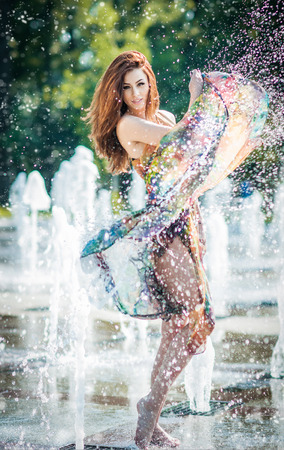 Attractive girl in multicolored short dress playing with water in a summer hottest day  Girl with wet dress enjoying fountains  Young beautiful happy female playing with outdoor water fountains