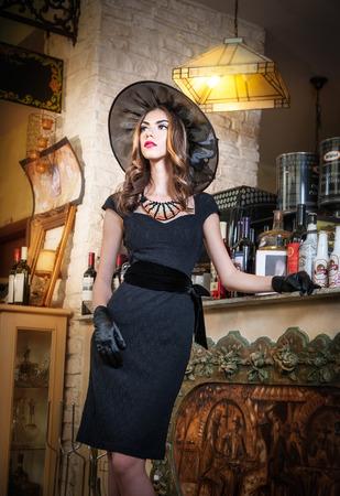 vedette de cin�ma: Belle jeune femme brune en posant noir avec �l�gance romantique myst�rieuse dame avec un regard de star de cin�ma dans de luxueux mill�sime int�rieur f�minin mode attrayant regardant comme une actrice am�ricaine