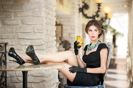 Fashionable attractive young woman in black dress sitting comfortable in restaurant Beautiful brunette relaxing with legs on table in vintage scenery with a juice glass Attractive lady with gloves