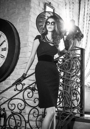 Young beautiful brunette woman in black standing on stairs near an over sized wall clock  Elegant romantic mysterious lady with movie star look in luxurious vintage interior, black and white photo  photo
