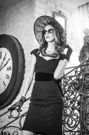 over sized: Young beautiful brunette woman in black standing on stairs near an over sized wall clock  Elegant romantic mysterious lady with movie star look in luxurious vintage interior, black and white photo  Stock Photo