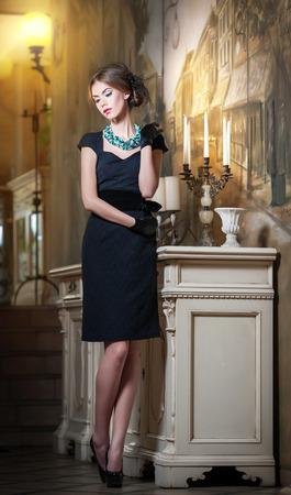 belle brunette: Belle jeune femme brune en robe noire élégante debout près d'un chandelier et le papier peint Sensuel dame romantique avec coiffure créative sur de hauts talons dans un intérieur luxueux de cru, rêvasser Banque d'images