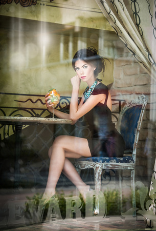 Fashionable attractive young woman in black dress sitting in restaurant, beyond the window  Beautiful brunette posing in elegant vintage scenery with a juice glass  Photo concept through the window