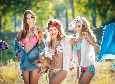Three sexy women with provocative outfits putting clothes to dry in sun  Sensual young females laughing putting out the washing to dry in sunny day  Perfect body housewives with a dog, shot in forest