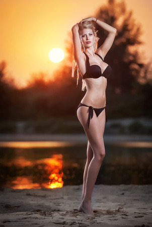 Portrait of young sexy blonde girl in bikini at the beach in sunset  Sensual attractive woman in black swimsuit on beach  Caucasian woman with perfect body relaxing on the beach photo