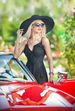 Outdoor summer portrait of stylish blonde vintage woman posing near red retro car  fashionable attractive fair hair female with black hat near a red vehicle  Sunny bright colors, outdoors shot  photo