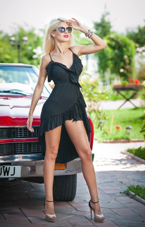 Summer portrait of stylish blonde vintage woman with long legs posing near red retro car  Fashionable attractive fair hair female near a red vintage vehicle  Sunny bright colors, outdoors shot  photo