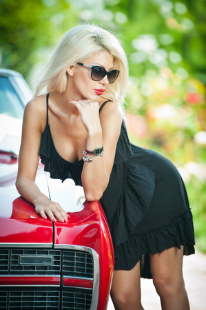 Summer portrait of stylish blonde vintage woman with black sunglasses bent over retro car  Fashionable attractive fair hair female leaning on red vintage vehicle   photo
