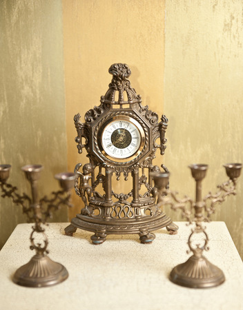 Golden vintage metallic clock with two candlesticks for three candles on white table.  Luxurious art objects: ancient clock and candelabras. Stock Photo