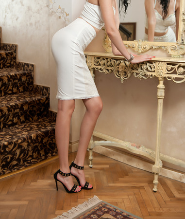 Beautiful young woman in short white tight fit skirt and corset looking into mirror. Perfect body female in front of a mirror, luxury scenery. Side view of sensual elegant woman on high heels sandals Stock Photo