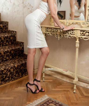 falda corta: Mujer joven hermosa en blanco corta apretada falda en forma y corsé mira en el espejo. Carrocería femenina perfecta en frente a un espejo, paisaje lujo. Vista lateral de la mujer elegante sensual en sandalias de tacón alto