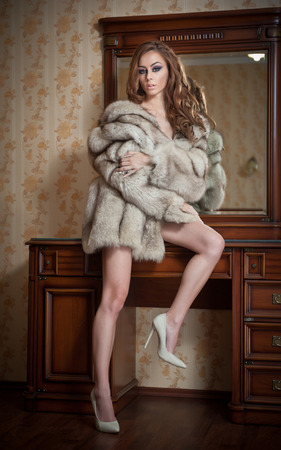 Attractive sexy young woman wearing only a fur coat posing provocatively indoor. Sensual redhead with long hair and high heels in front of a mirror. Beautiful girl with fur coat and long legs posing photo