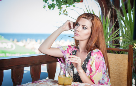 Attractive red hair young woman with bright colored blouse drinking lemonade on a terrace having blue sea in background. Gorgeous redhead model drinking fresh drink with straw in a summer day photo