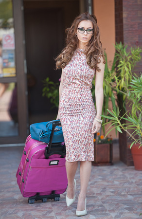 Beautiful woman with suitcases leaving the hotel in a big city. Attractive redhead with sunglasses and elegant dress on street carrying a suitcase. Young fashionable female with her luggage urban shot photo
