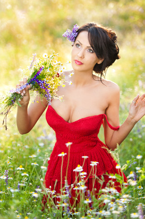 low blouse: Young voluptuous brunette holding a wild flowers bouquet in a sunny day. Portrait of beautiful woman with low-cut red dress posing, outdoor shot. Provocative female enjoying the nature Stock Photo